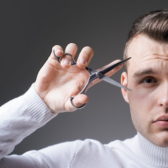 Haare schneiden. mann strenge gesicht halten schere. barber glänzende frisur halten stahlschere. kreieren sie ihren stil. macho selbstbewusster friseur schnitt haare. barbershop-servicekonzept. professionelle friseurausrüstung.