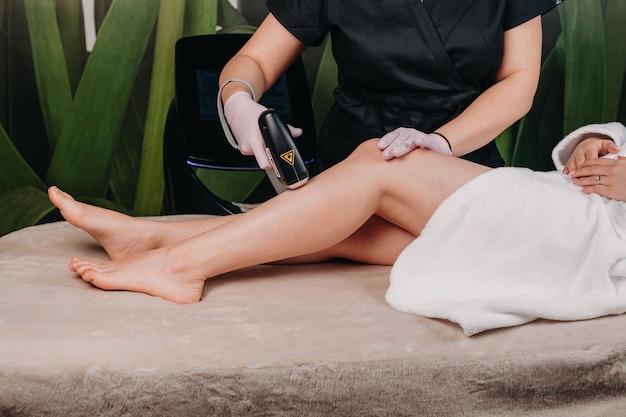 Haarentfernungsbehandlung am bein mit laser, durchgeführt von einem sorgfältigen dermatologen im spa-salon