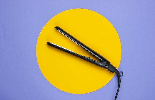 Haarglätter auf einem lila mit gelbem kreis in der mitte