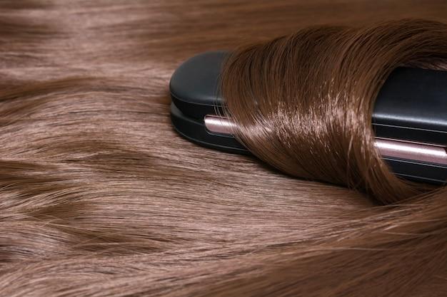 Haarglätter. brillant glattes schönes haar und lockenwickler.