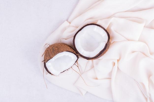 Haarige kokosnuss auf weißer tischdecke in zwei hälften zerbrochen.
