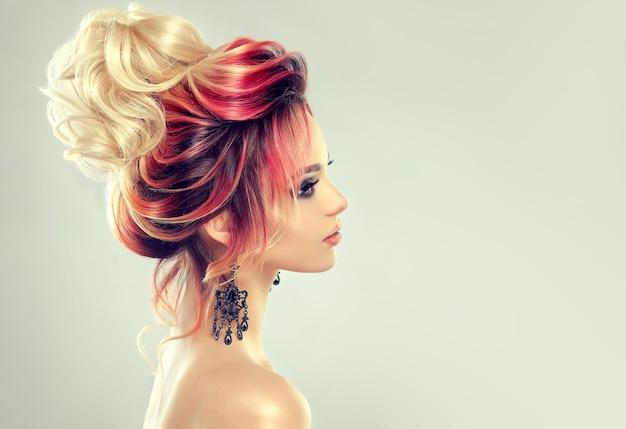 Haarmalerei. junge attraktive frau mit mehrfarbigem haar gesammelt in eleganter abendfrisur mit großem blondem brötchen. friseur und färbung der haare