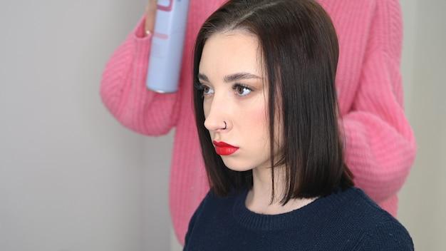 Haarmeister sprüht lack, macht styling. attraktive brünette im schönheitssalon.