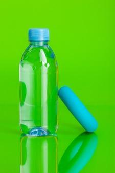Haarscharfes wasser in einer flasche auf grünem hintergrund