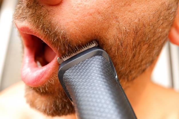 Haarschneidemaschine pflegte, den bart eines mannes mit wenig geld zu schneiden, um sich zu retten, zum friseur zu gehen.