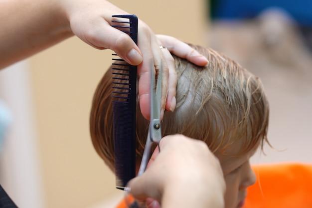 Haarschnitt eines kleinen jungen in einem frisörsalon der kinder