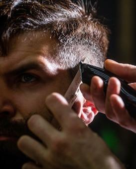Haarschnitt-konzept hipster-kunde, der haarschnitt-mann besucht, der friseur in friseursalon-friseurarbeit besucht