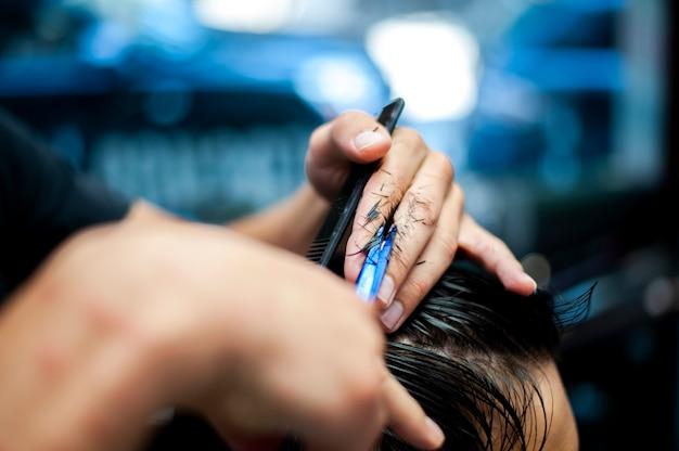 Haarschnitt mit der unscharfen hand des friseurs