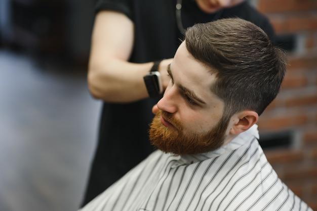 Haarschnitt perfekt aussehen lassen. junger bärtiger mann, der haarschnitt durch friseur erhält, während im stuhl am friseursalon sitzt