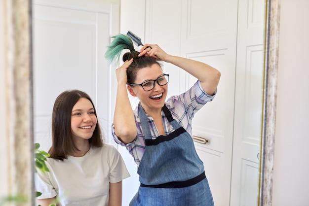 Haarschnitt zu hause, mama schneidet töchtern die haare, frau schneidet ungesundes gefärbtes haar, mutter zeigt geschnittenes gefärbtes haar, mädchen glücklich mit neuem haarschnitt