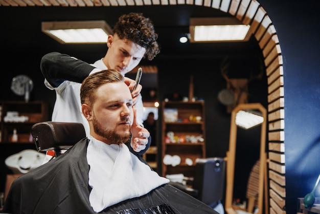 Haarstyling und haarschneiden für männer in einem friseurladen oder friseursalon.