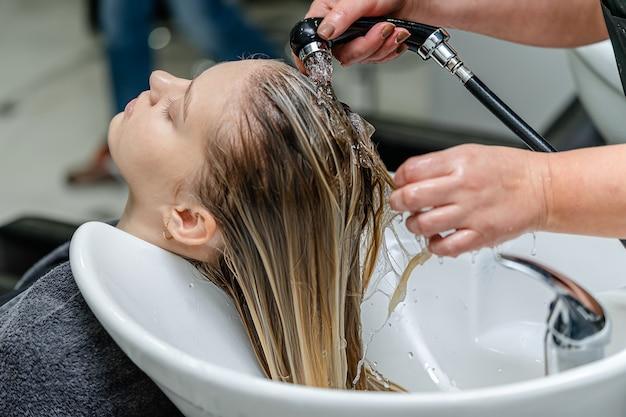 Haarstylist, der haare einer jungen hübschen frau in einem schönheitssalon wäscht.