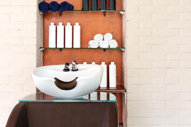 Haarwaschbecken zum waschen von haaren im schönheitssalon oder friseurladen, shampoos, handtücher. friseur stylist arbeitsbereich. friseurschale, haarwaschausrüstung. beauty salon interieur mit kopierraum