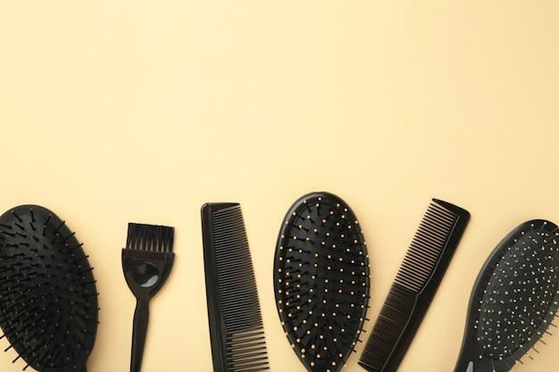 Haarwerkzeuge, schönheits- und friseurkonzept - verschiedene bürsten oder kämme auf beiger oberfläche