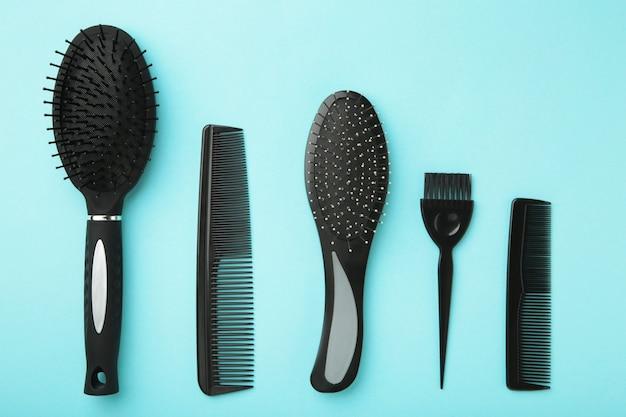 Haarwerkzeuge, schönheits- und friseurkonzept - verschiedene bürsten oder kämme auf blauer oberfläche