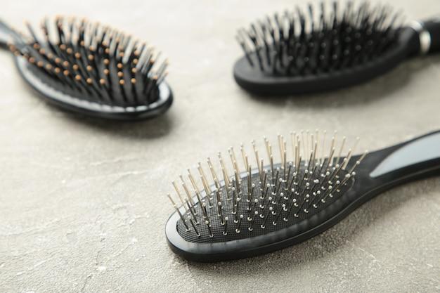 Haarwerkzeuge, schönheits- und friseurkonzept - verschiedene bürsten oder kämme auf grauer oberfläche