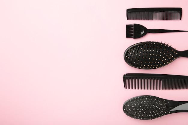 Haarwerkzeuge, schönheits- und friseurkonzept - verschiedene pinsel oder kämme auf rosa oberfläche mit kopierraum