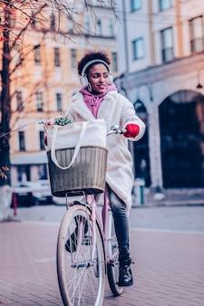 Hab einen traum. hübsche junge frau, die lächeln auf ihrem gesicht hält, während fahrrad fährt
