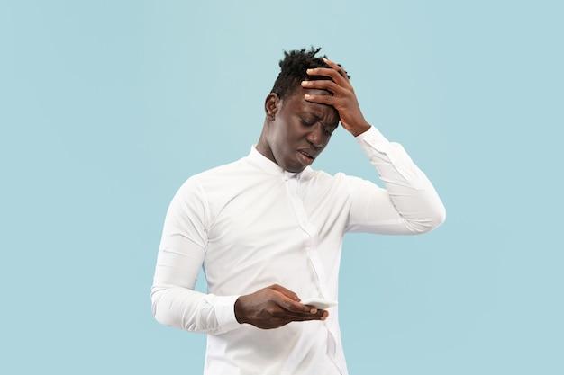 Habe gerade eine wette verloren. junger afroamerikanischer mann mit smartphone isoliert auf blauem studio, gesichtsausdruck.