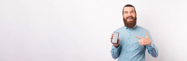 Haben sie diese nachrichten gehört? bärtiger mann, der auf seinen telefonbildschirm zeigt.