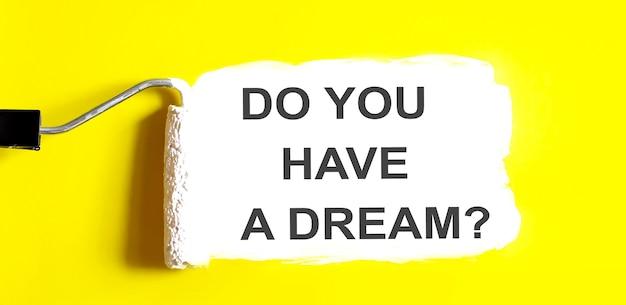 Haben sie einen traum. eine geöffnete dose farbe mit weißem pinsel auf gelbem hintergrund.