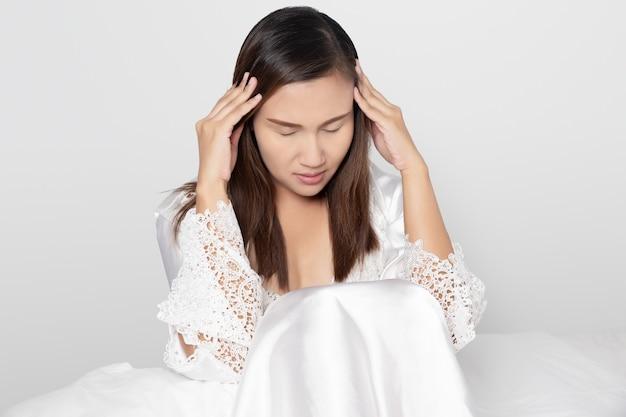 Haben sie kopfschmerzen, auf einem grauen hintergrund, frauen in weißem nachthemd & langarm satin robe mit floraler spitze schwindlig bis schlaflosigkeit auf dem weißen bett im schlafzimmer.