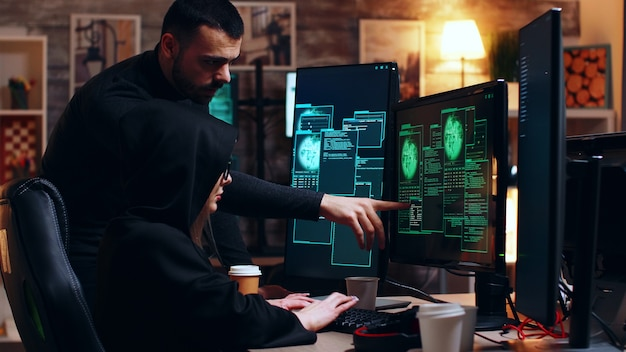 Hacker-anführer, der mädchen bei ihrem hacken mit einem gefährlichen virus hilft.