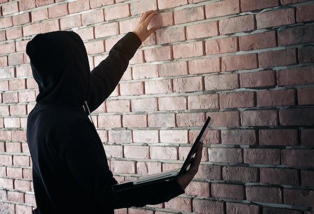 Hacker, der an seinem computer arbeitet. schwarzer maskierter hacker im schwarzen langen hülsenhemd ist geschnürt