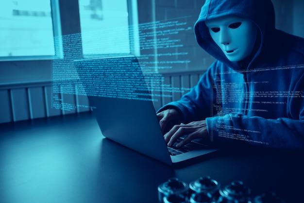 Hacker der asiatischen leute tragen eine maske unter verwendung eines laptopcyberangriffs.