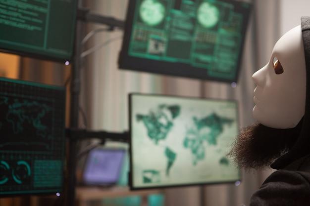 Hacker, der eine weiße maske trägt, um seine identität zu schützen und eine gefährliche malware zu erstellen.