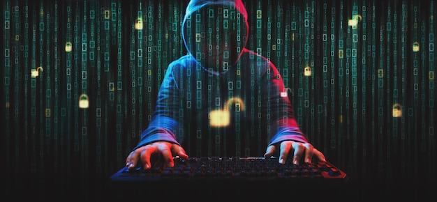 Hacker im dunklen hoodie-thema. hacker auf dem bildschirm mit binärcode Premium Fotos