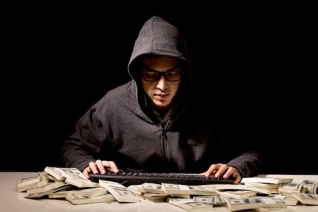 Hacker in einer haube, die informationen mit computer auf dunklem hintergrund stiehlt