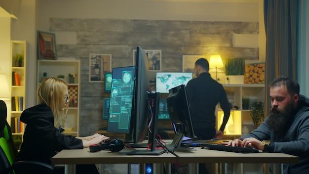 Hacker-mädchen mit ihrem team, das online-informationen mit supercomputern stiehlt.