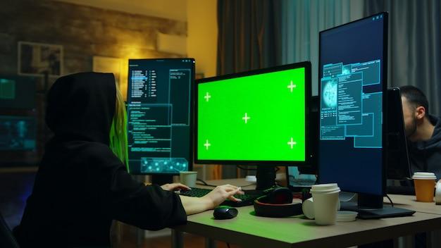 Hacker-mädchen trägt einen schwarzen hoodie vor computer mit grünem bildschirm. identitätsdiebstahl.