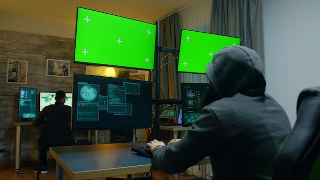 Hacker mit kapuzenpullis, der eine gefährliche malware auf computer mit grünem bildschirm macht.