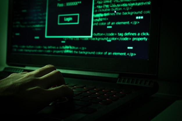 Hacker mit laptop in dunklem web.