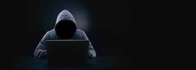 Hacker ohne gesicht in einer kapuze auf dunkelheit