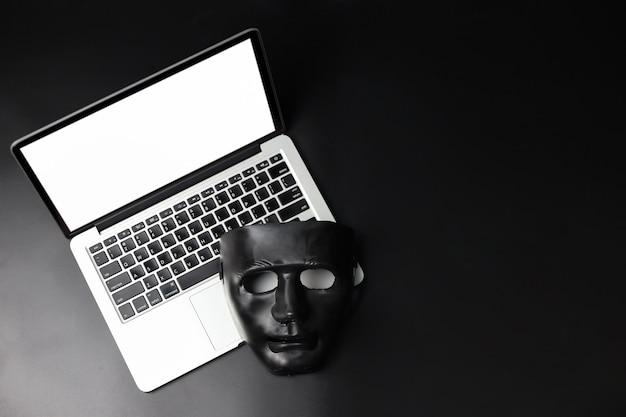 Hacker- und cyberkriminalitätskonzept, schwarze maske auf neuem computer mit weißem bildschirm auf schwarzem hintergrund