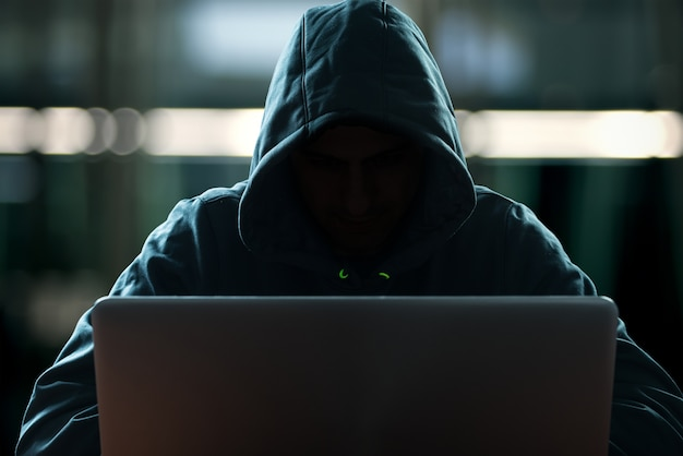 Hacker vor seinem computer. dunkles gesicht