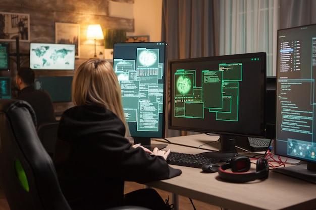 Hackerin, die tastatur verwendet, um eine gefährliche malware in das banksystem einzugeben.