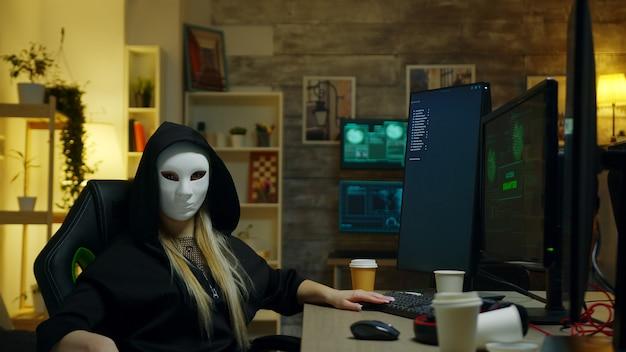 Hackermädchen, das eine weiße maske trägt, während es mit einem supercomputer cyberkriminalität begeht.