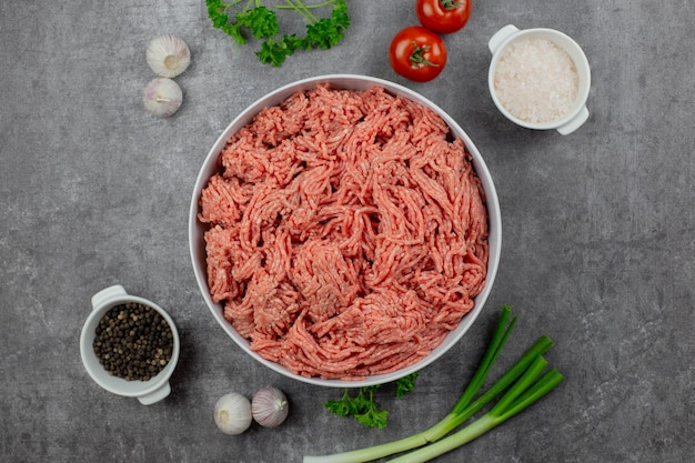 Hackfleisch, hackfleisch mit zutaten zum kochen mit gewürzen, meersalz, schwarzen pfefferkörnern und kräutern auf dunklem betonhintergrund.