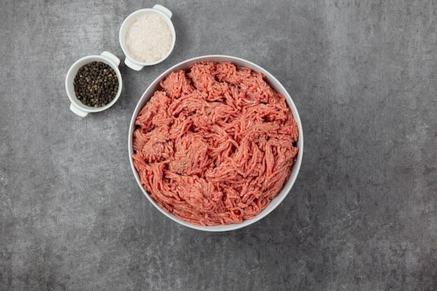 Hackfleisch, hackfleisch mit zutaten zum kochen mit gewürzen, meersalz und schwarzen pfefferkörnern auf dunklem betonhintergrund.