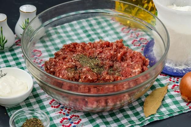 Hackfleisch liegt in einer transparenten schüssel auf dem tisch und wird für fleischbällchen und deren weiteres backen im ofen in horizontaler ausrichtung zubereitet