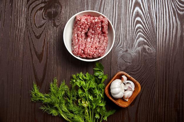 Hackfleisch mit frischen gewürzen auf einem holztisch