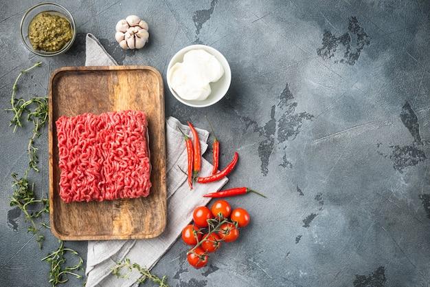 Hackfleischmischung für fleischbällchen und zutaten auf grauem steintisch, draufsicht flach gelegt