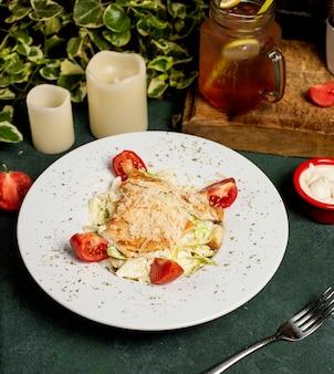 Hähnchen-caesar-salat mit gehacktem parmesan, salat und tomaten