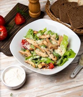 Hähnchen-parmesan-caesar-salat mit salat, kirschtomaten in einer weißen schüssel, serviert mit sauce und brot.