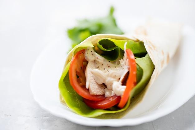Hähnchen-salat-tortilla-wraps auf weißem teller auf keramik