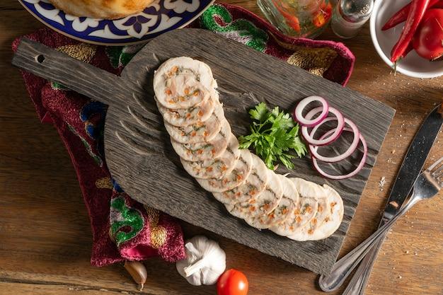 Hähnchenbrötchen mit suluguni-käse, karotten, kräutern, walnüssen, gewürzen, koriander und roten zwiebeln, gehackt und auf einem hölzernen schneidebrett serviert.